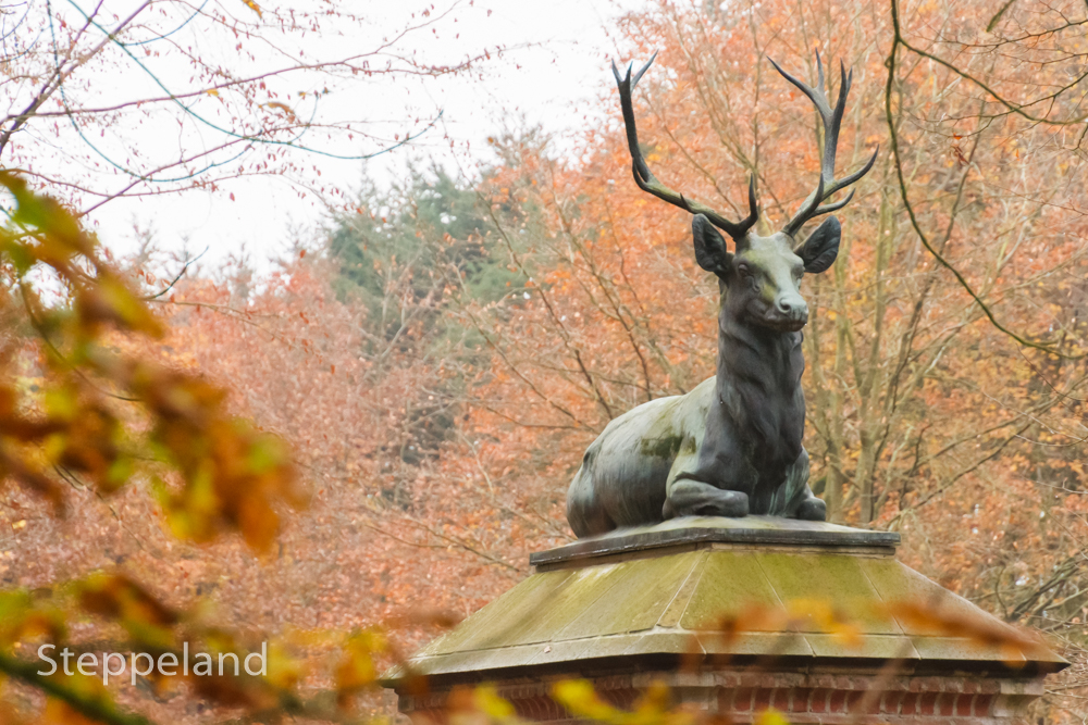 Majestic deer statue on a gate post in the Palace woods