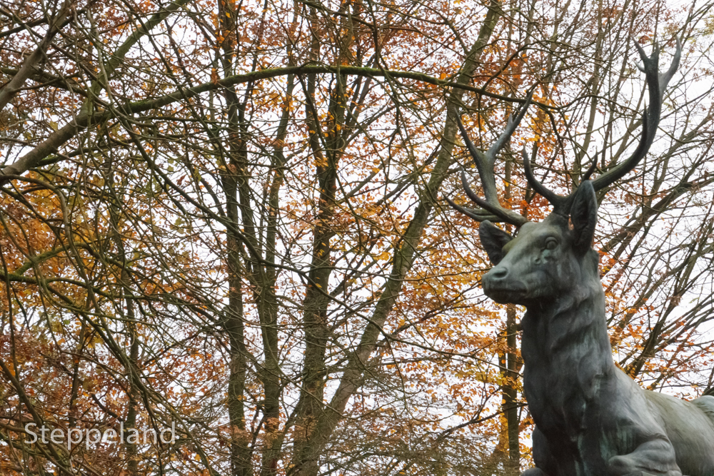 Profile of the deer statue in the autumn woods